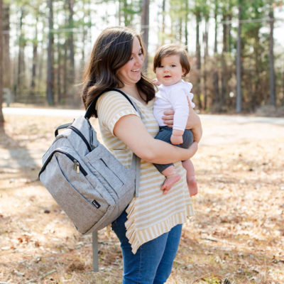 White Mom in a yellow and white striped shirt and denim stands in a wooded area wearing Katie Diaper Bag and holding baby